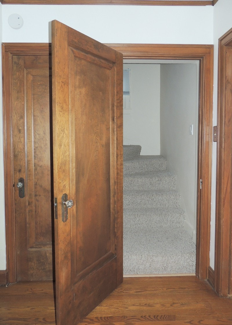 """Door on the left is to the large unfinished basement. Door on the right is upstairs to what we imagine as the """"master suite."""""""