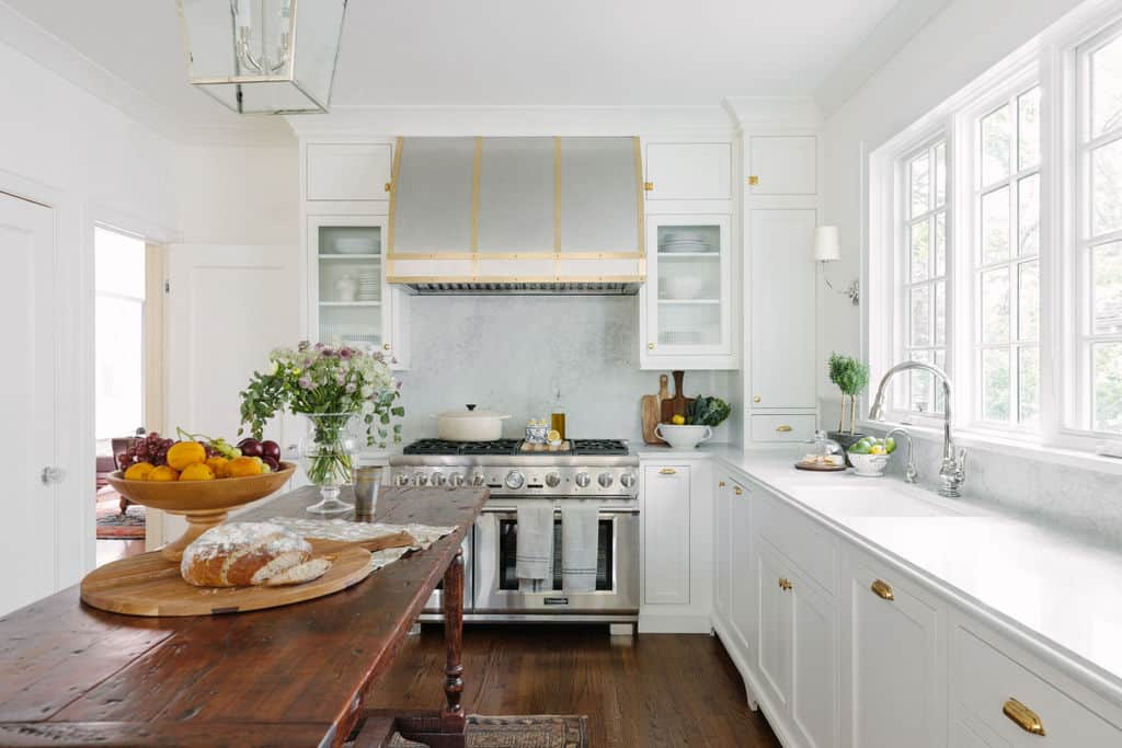 white kitchen with wood island and commercial hood